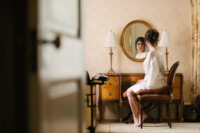 Bride looks into mirror as she gets ready for her wedding at Cairnwood Estate