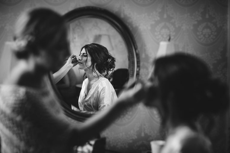 Black and white image of bride having make up done at Cairnwood Estate in Bryn Athyn, PA.