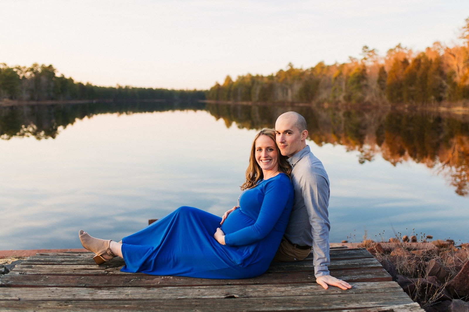 Mom and Dad sit by the lake at Batsto Village in NJ at sunset maternity session.
